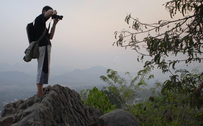 Junger Wanderer, Reisender, der Fotos bei Sonnenuntergang, Luang Prabang Gipfel macht stockfotos