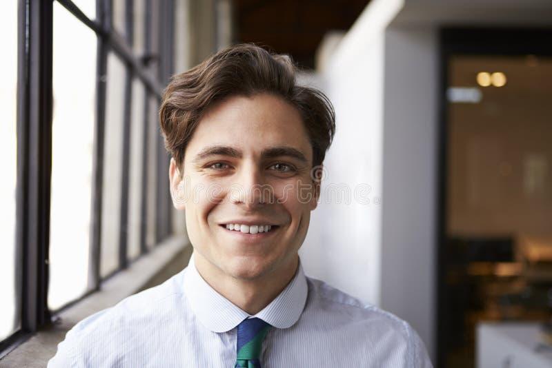 Junger weißer Geschäftsmann, der zur Kamera, Porträt lächelt stockbild