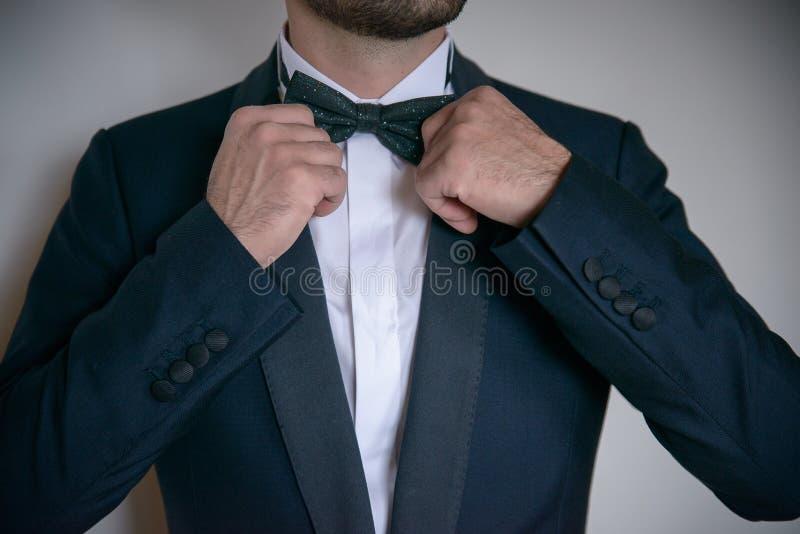 Junger weißer kaukasischer Mann, der seine Fliege in Bestellung einsetzt und formale, elegante Kleidung trägt stockfotografie