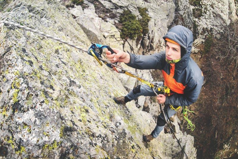 Junger weißer Mann, der eine steile Wand in den Bergen, kletternder extremer Sport, horizontale Weitwinkelorientierung klettert stockfotos
