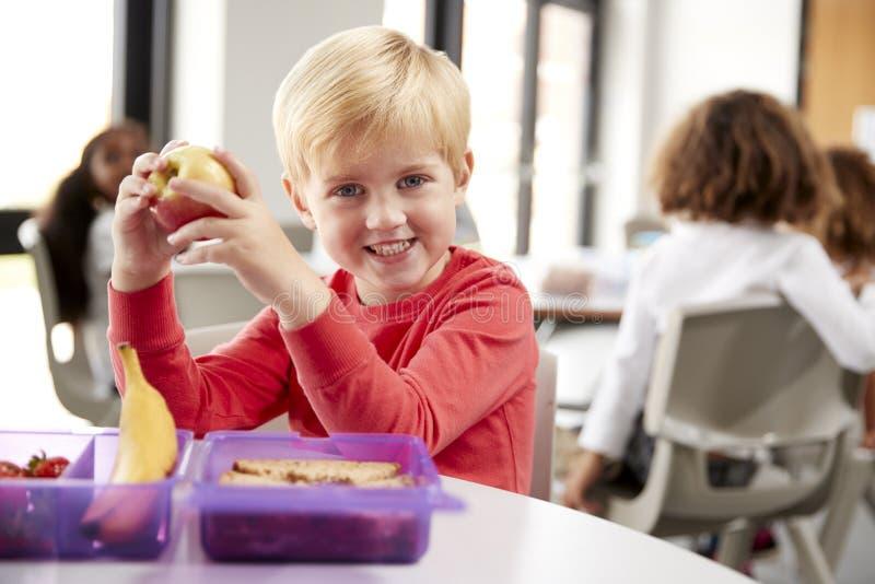Junger weißer Schüler, der an einem Tisch lächelt und hochhält einen Apfel in einem Kindergartenklassenzimmer während seiner Mitt stockbilder