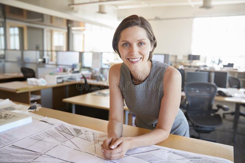 Junger weiblicher Architekt, der auf dem Schreibtisch lächelt zur Kamera sich lehnt stockfotografie