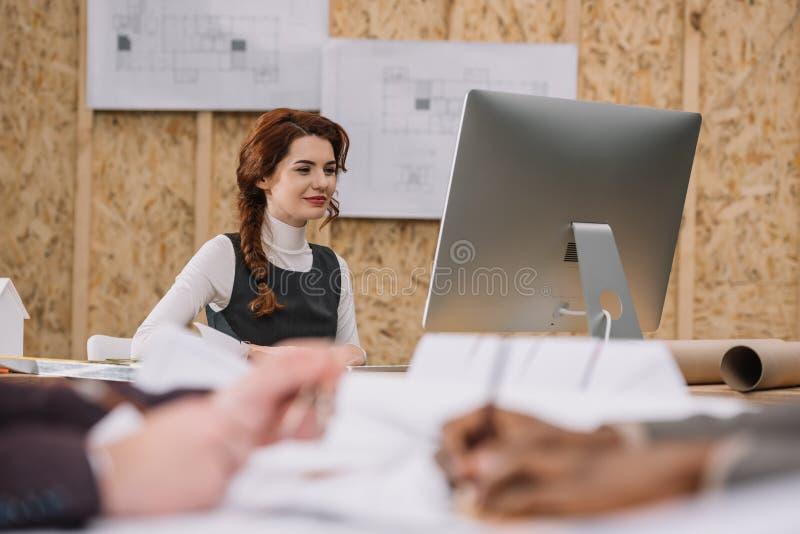 junger weiblicher Architekt, der mit Computer im Büro arbeitet, während Kollegen drawong plant lizenzfreies stockbild