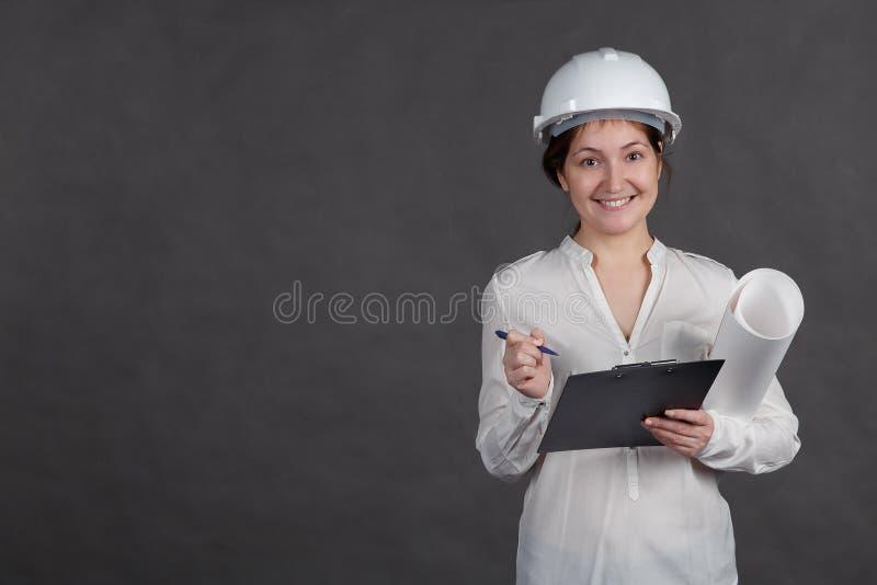 Junger weiblicher Architekt in einem Schutzhelm macht Anmerkungen auf dem Projekt mit einem Papier in den Händen lizenzfreies stockbild
