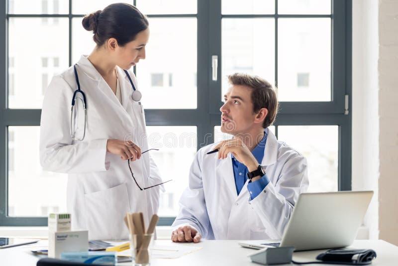Junger weiblicher Arzt, der um Rat von ihrem erfahrenen MA bittet lizenzfreies stockbild