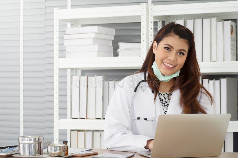 Junger weiblicher Arzt weißen Mantel mit Stethoskop unter Verwendung des Laptops beim Arbeiten tragen am Prüfungsraum, -gesundhei stockbilder