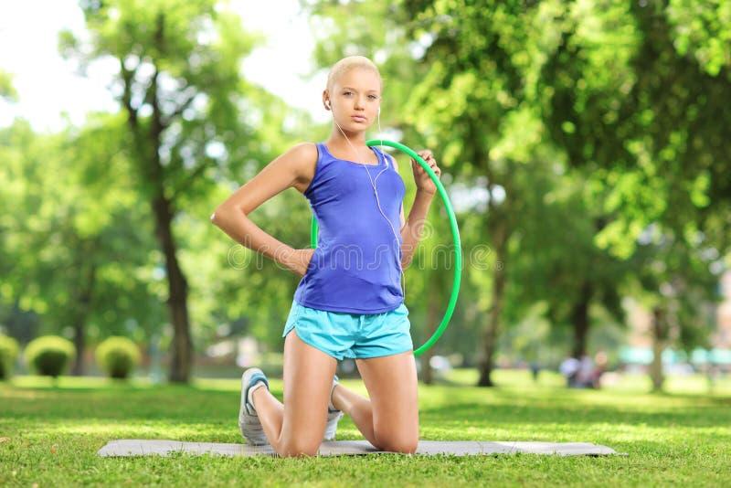 Junger weiblicher Athlet auf einer Matte, die ein hula Band in einem Park hält lizenzfreie stockbilder