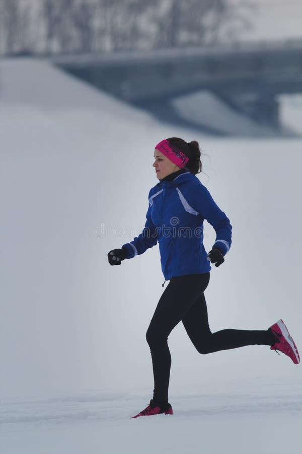 Junger weiblicher Athlet, der mit Sorgfalt in Winter durch den Schnee läuft lizenzfreie stockfotos