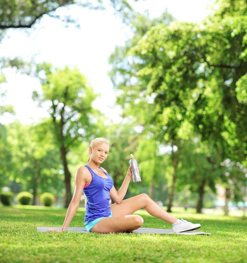 Junger weiblicher Athlet, der nach Übung sitzt und Flasche hält lizenzfreie stockfotos