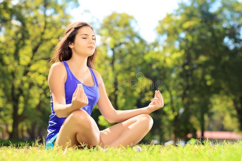 Junger weiblicher Athlet in der Sportkleidung meditierend in einem Park stockbilder