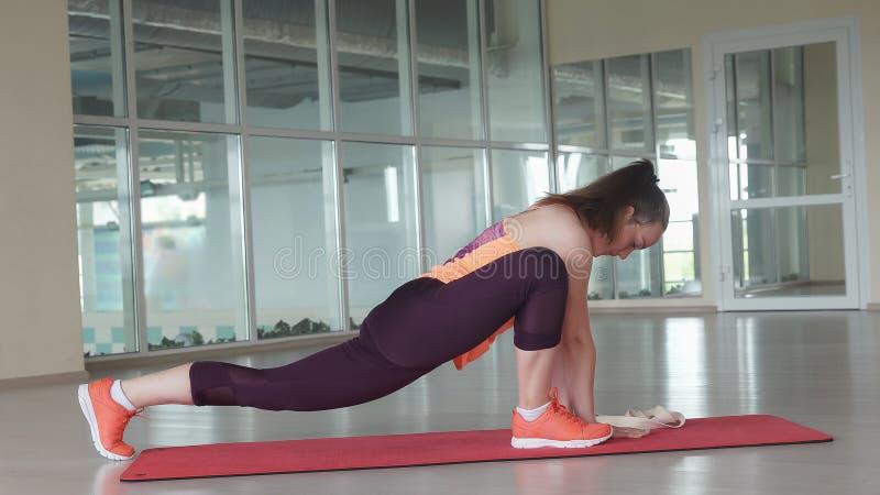 Junger weiblicher Athlet macht schwierige ausdehnende Übung auf Turnhallenmatte bei der Ausbildung in der Turnhalle lizenzfreies stockfoto