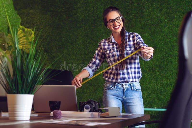 Junger weiblicher Auftragnehmer, der in ihrem Büro auf einem neuen Projekt arbeitet lizenzfreies stockbild