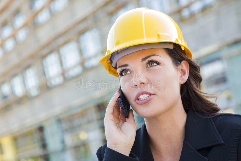 Junger weiblicher Auftragnehmer-tragender Schutzhelm auf Standort unter Verwendung des Telefons stockbilder