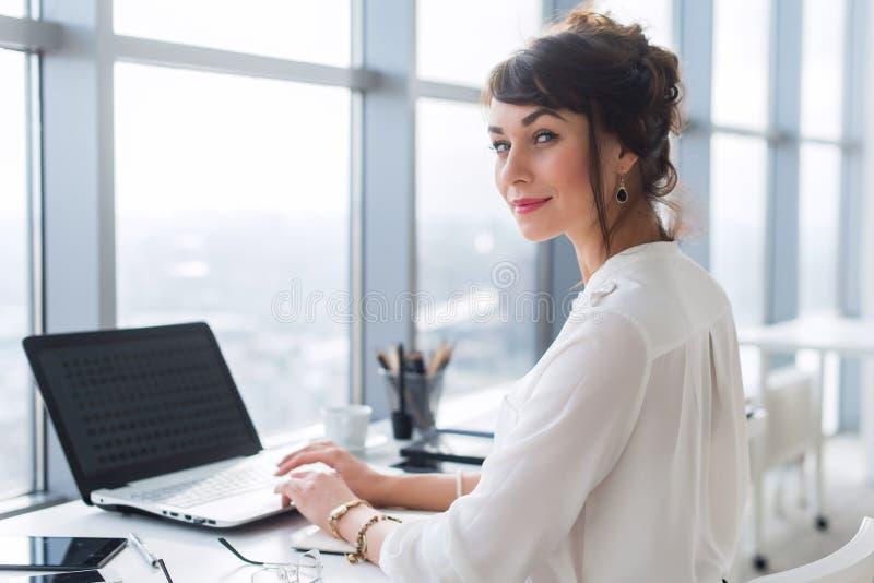 Junger weiblicher Büroangestellter, der Laptop bei der Arbeit, Lächeln, Kamera schauend verwendet Geschäftsfrau, die, blogging wä lizenzfreie stockfotos