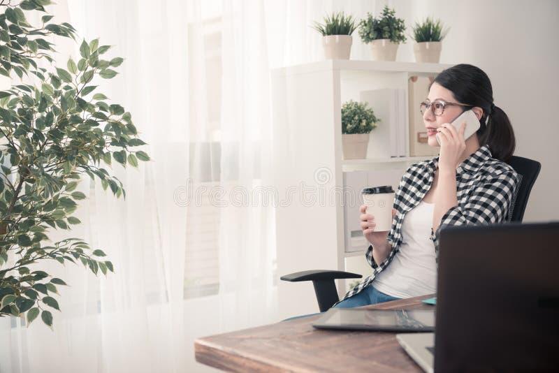 Junger weiblicher Büroangestellter, der Mobilhandy verwendet lizenzfreies stockbild