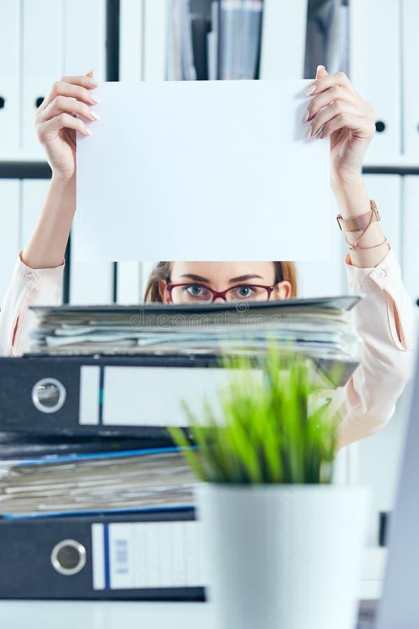 Junger weiblicher Büroangestellter versteckt sich hinter dem Ordner, der das saubere weiße Blatt Papier hält Konzept der schlecht lizenzfreies stockbild