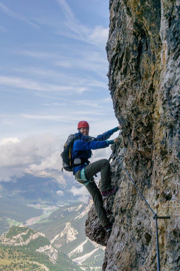 Junger weiblicher Bergsteiger auf einer Vertikale und herausgestellten einer Felsenwand stockbild