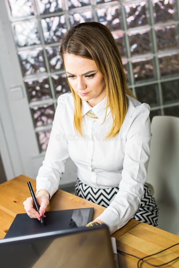 Junger weiblicher Designer, der Grafiktablette beim Arbeiten mit Computer verwendet lizenzfreie stockfotos