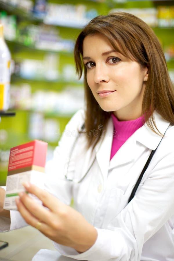 Junger weiblicher Doktor beim Apothekelächeln lizenzfreie stockfotos