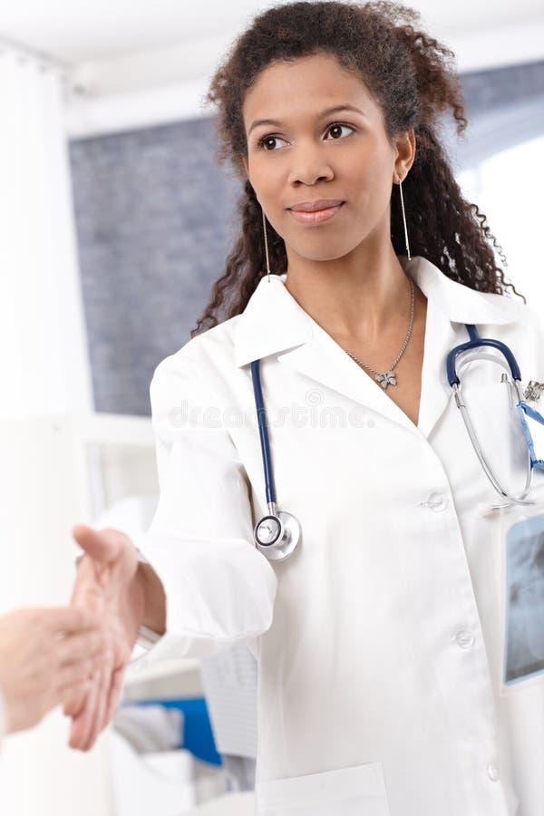 Junger weiblicher Doktor, der Hände rüttelt lizenzfreies stockbild