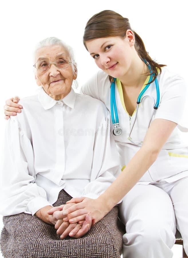 Doktor, der um einer alten Dame sich kümmert lizenzfreies stockbild