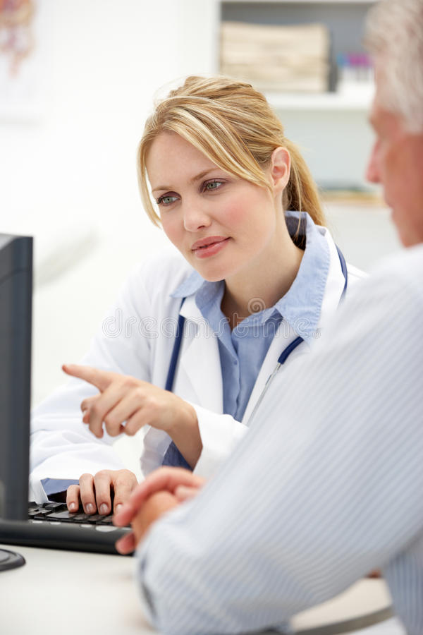 Junger weiblicher Doktor mit älterem Patienten stockfotos