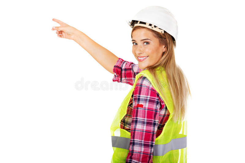 Junger weiblicher Erbauer, der für etwas zeigt stockfotos