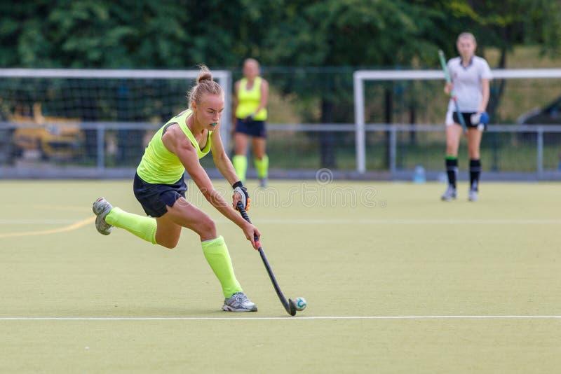 Junger weiblicher f?hrender Ball des Hockeyspielers im Angriff stockbilder