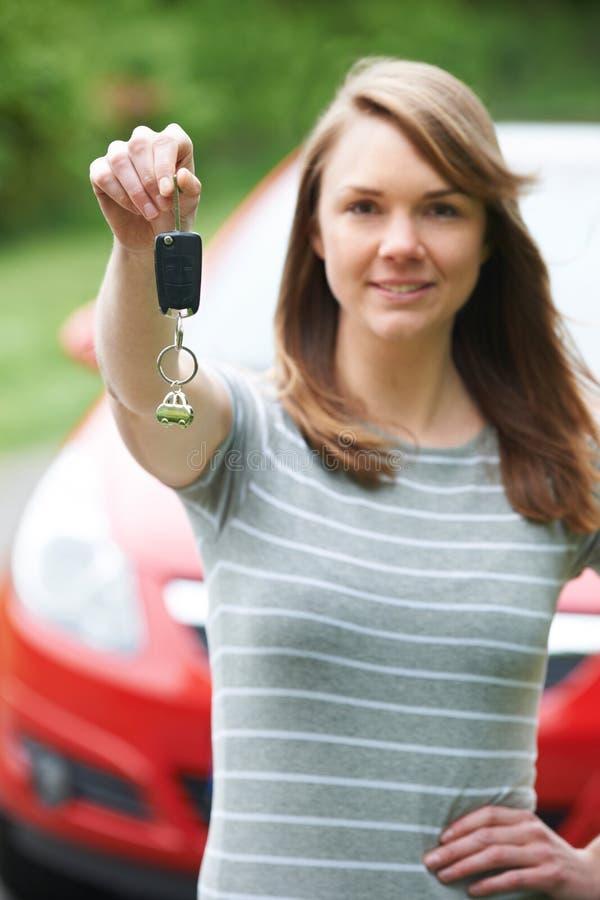 Junger weiblicher Fahrer Holding Car Keys in Front Of Vehicle lizenzfreie stockbilder