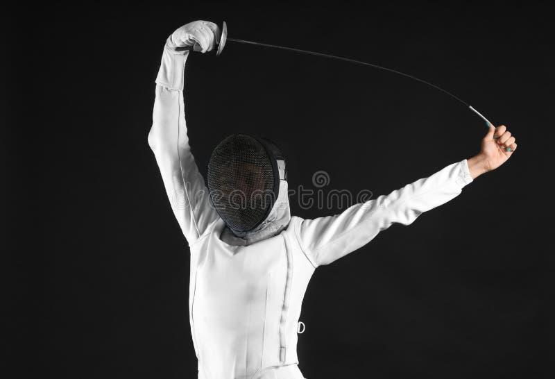 Junger weiblicher Fechter auf dunklem Hintergrund stockbild