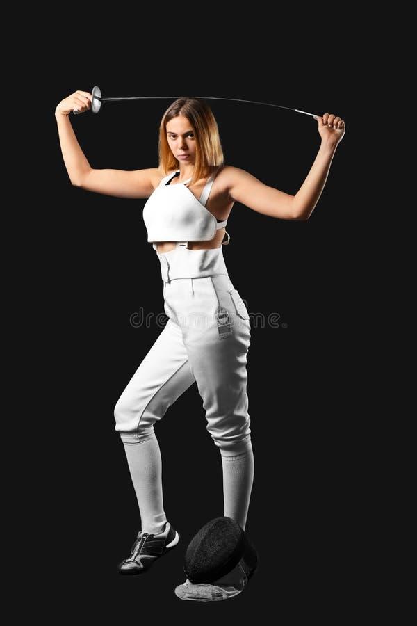 Junger weiblicher Fechter auf dunklem Hintergrund stockfotos