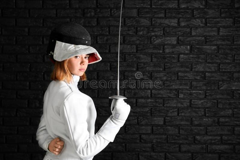 Junger weiblicher Fechter auf dunklem Hintergrund stockbilder