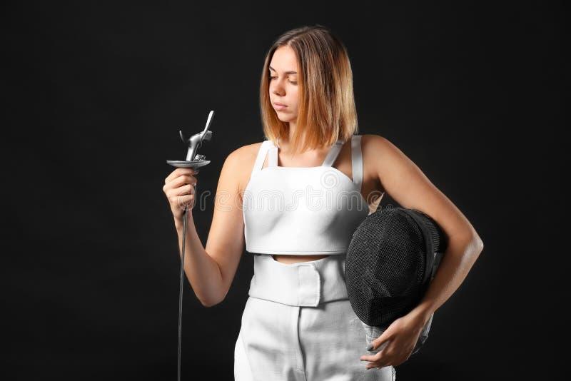 Junger weiblicher Fechter auf dunklem Hintergrund stockfoto