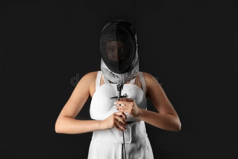 Junger weiblicher Fechter auf dunklem Hintergrund lizenzfreies stockfoto