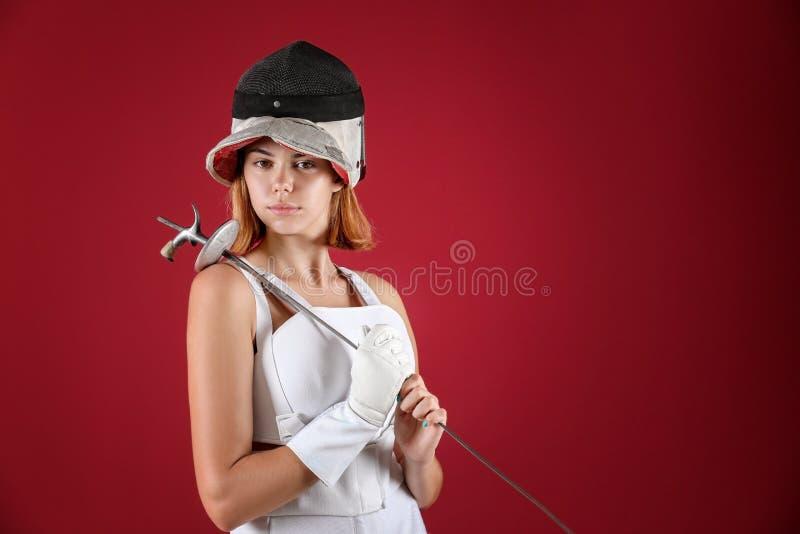 Junger weiblicher Fechter auf Farbhintergrund stockfoto