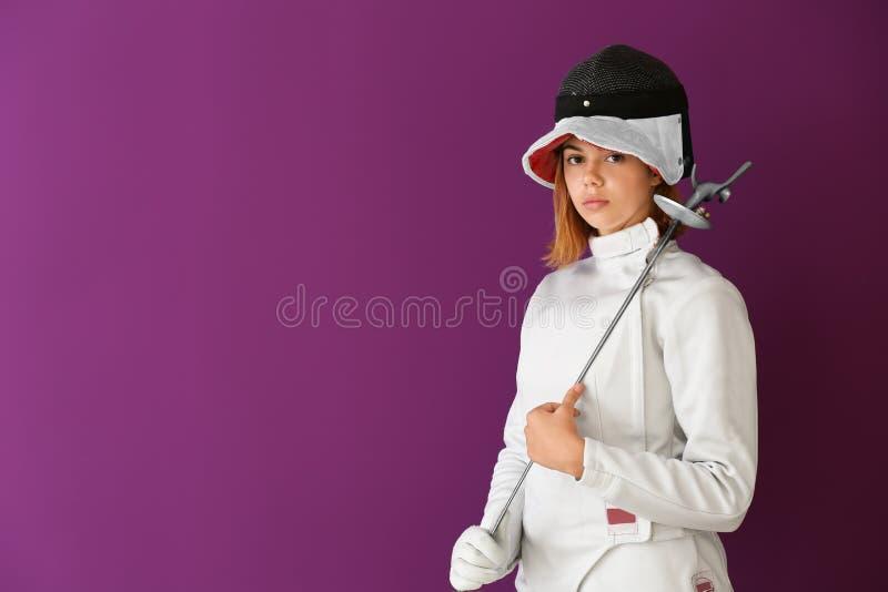 Junger weiblicher Fechter auf Farbhintergrund stockbilder
