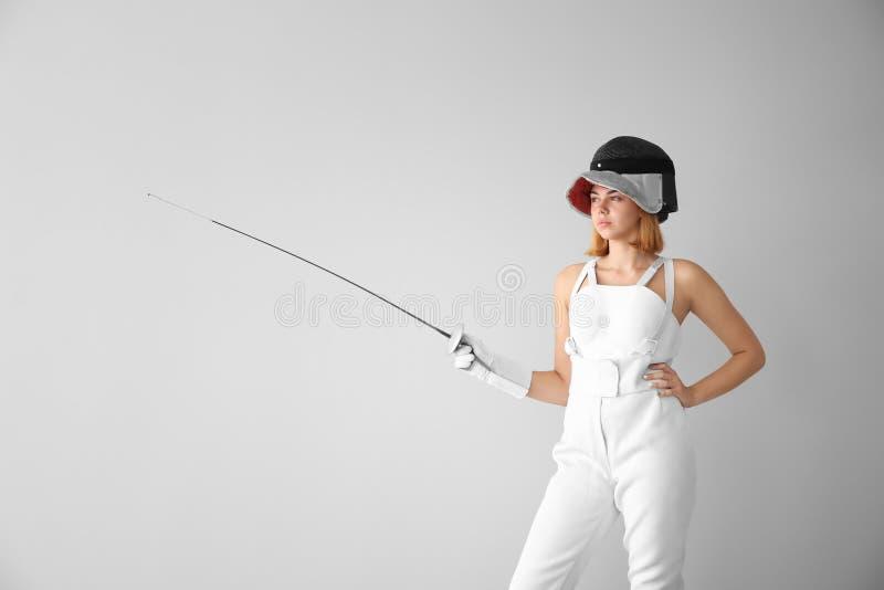 Junger weiblicher Fechter auf hellem Hintergrund lizenzfreie stockbilder