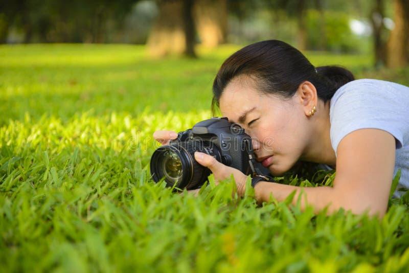 Junger weiblicher Fotograf, der draußen Foto mit Berufskamera auf Gras macht stockbild