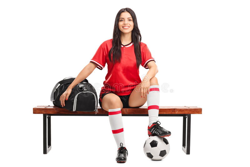 Junger weiblicher Fußballspieler, der auf einer Bank sitzt stockfotografie