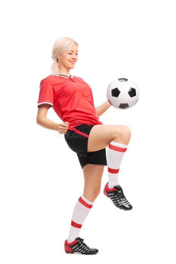 Junger weiblicher Fußballspieler, der einen Ball jongliert stockfotografie