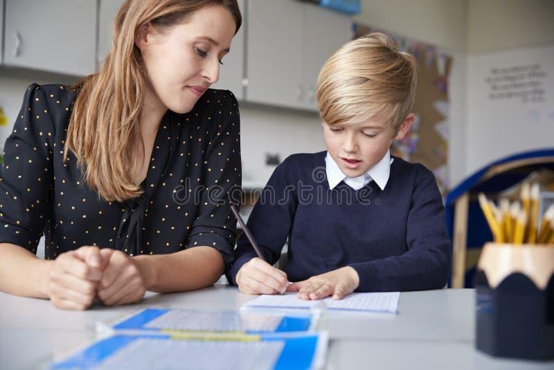Junger weiblicher Grundschullehrer und Schüler, die an einem Tisch bearbeitet ein auf einem, unten oben schauend, Vorderansicht,  stockbild