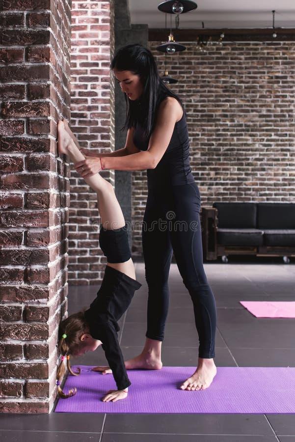 Junger weiblicher Gymnastiklehrer, der das Kindermädchen tut Handstand gegen Wand unterstützt stockbild