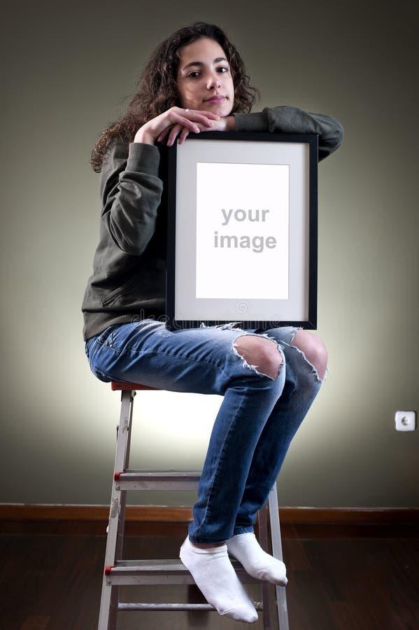 Junger weiblicher haltener Bilderrahmen lizenzfreie stockbilder