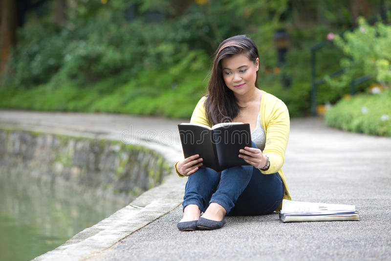 Junger weiblicher Hochschul- oder Student, der ein Buch, gesetzt durch einen See in einem Park liest stockbild