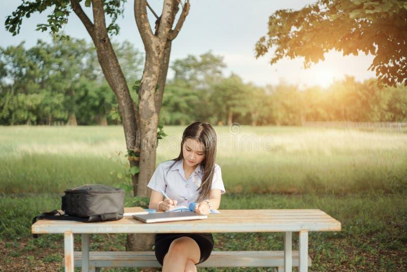 Junger weiblicher Hochschulstudent schreibt eine Anmerkung und eine Aufgabe mit einem Laptop dazu außerhalb des Campus mit grünem stockfotografie
