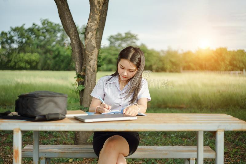 Junger weiblicher Hochschulstudent schreibt eine Anmerkung und eine Aufgabe mit einem Laptop dazu außerhalb des Campus mit grünem stockbilder