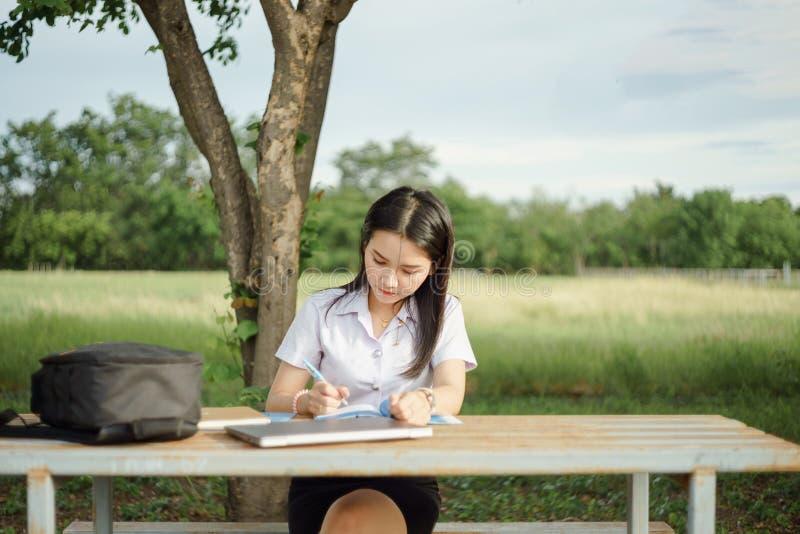 Junger weiblicher Hochschulstudent schreibt eine Anmerkung und eine Aufgabe mit einem Laptop dazu außerhalb des Campus mit grünem lizenzfreies stockfoto