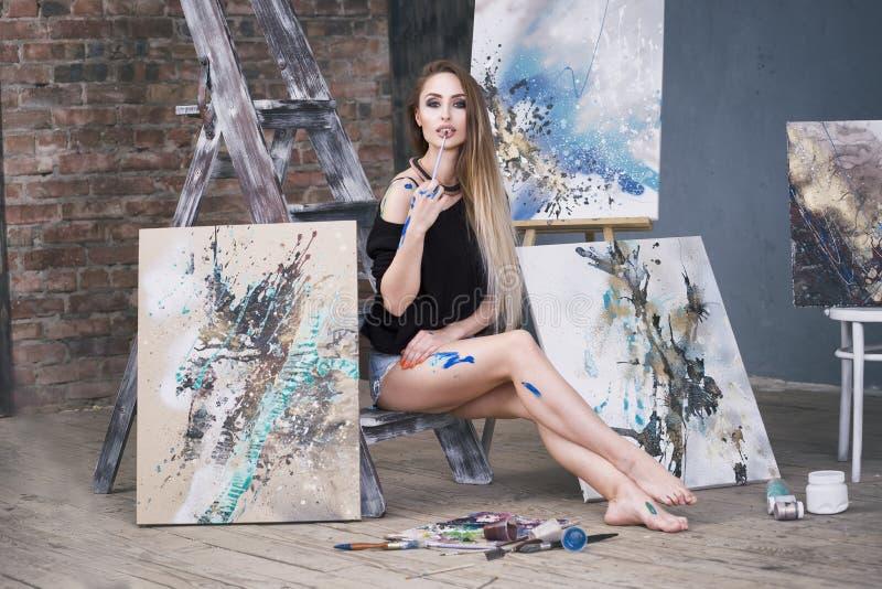 Junger weiblicher Künstler, der abstraktes Bild im Studio, schönes sexy Frauenporträt malt lizenzfreies stockfoto