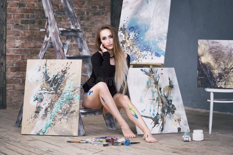 Junger weiblicher Künstler, der abstraktes Bild im Studio, schönes sexy Frauenporträt malt stockbilder