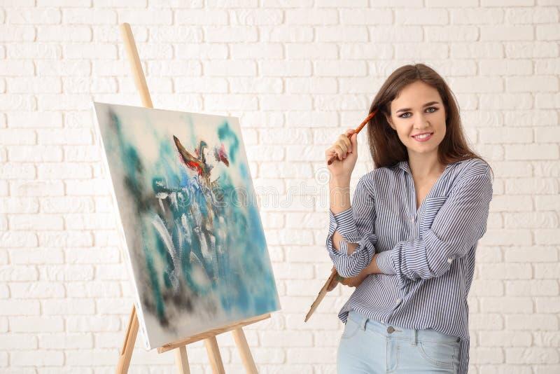 Junger weiblicher Künstler mit Zeichnungsgestell gegen weiße Backsteinmauer lizenzfreie stockbilder